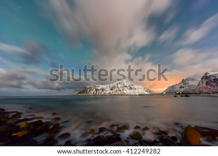 Northern lights over the sea at Skagsanden Beach, Lofoten Islands, Norway in the winter.