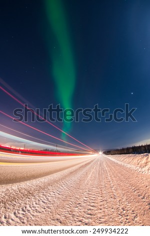 Northern lights over winter road with light trails from moving cars near Apatity and Kirovsk towns in Murmansk region (Kola peninsula) in northern Russia - long exposure nature background - stock photo