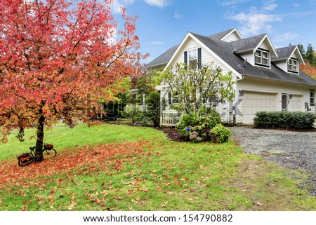 Northwest horse ranch white house with fall changing leaves and white fence. - stock photo