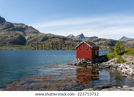 Norway landscape with red fishing house and deep blue sky.