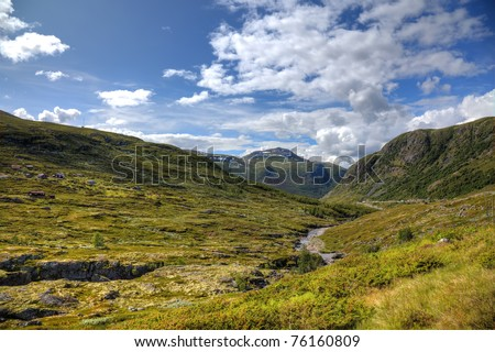 Norway mountain. Norwegian landscape. Grass, river, spring, farm meadow in Norway. Scandinavian norwegian hike landscape. Wide angle sky, mountains, hill, rocks landscape of Norway Scandinavian Europe - stock photo