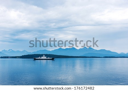 Norway. Remote view at the ferry on the fjord in a overcast day - stock photo
