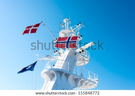 Norwegian and Danish flag on a cruise ship mast tower flying in the wind over blue sky - stock photo