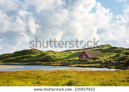 Norwegian cloudy landscape with small house and a river - stock photo