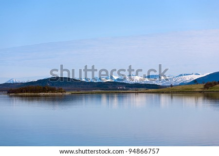 Norwegian coast landscape with snow on the mountain - stock photo