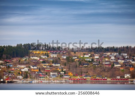 Norwegian coastal town landscape with colorful wooden houses and boats - stock photo