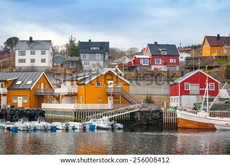 Norwegian fishing village, wooden houses on the sea coast and moored boats - stock photo