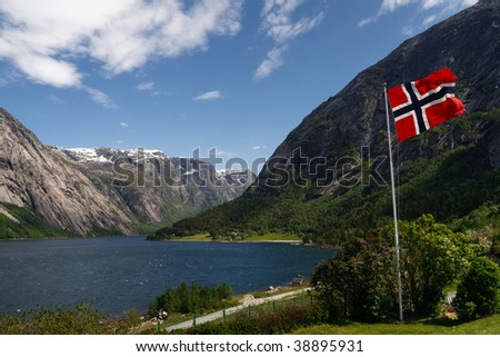 Norwegian flag in the foreground. Majestic Hardangerfjord as seen from the village of Eidfjord in the background. - stock photo