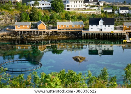 Norwegian houses reflected in the water - stock photo