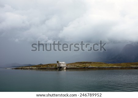 Norwegian landscape at Helgeland coast, Norway. Old wooden boathouse is in bad condition, some planks are laying around and a tree grows at roof.  - stock photo