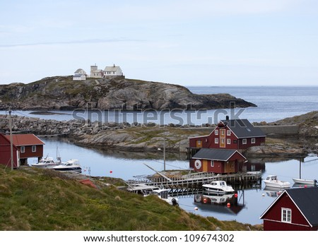 Norwegian rorbu fishing houses and boats on Bjornsund - stock photo