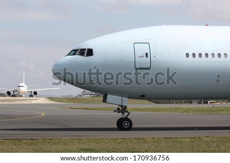Nose of huge airplane with second airplane in background - stock photo