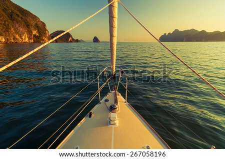 Nose of yacht sailing in the sea at sunset