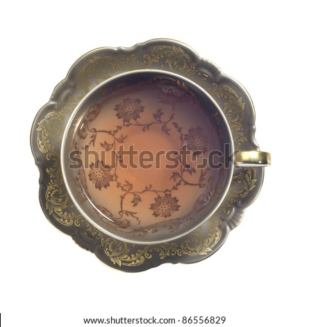 nostalgic ornamented tea cup filled with tea. Studio photography seen from above, isolated on white with clipping path