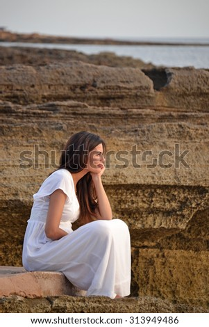 Nostalgic serene woman on white dress sitting on rocks looking at the sea sunset.