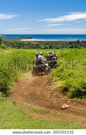 NOSY BE, MADAGASCAR - APR 10: Group of tourists riding quad on Nosy Be island, Madagascar on apr 10, 2008. - stock photo