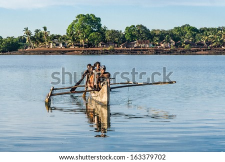 NOSY BE, MADAGASCAR - APR 4: unidentified people crossing the inlets in an outrigger canoe on april 4, 2008 - stock photo