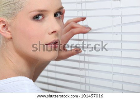 Nosy blond peering through window blinds - stock photo