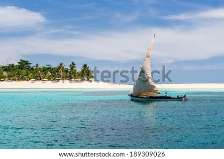 NOSY IRANJA, MADAGASCAR - APR 5: Fishing boat passing by the beach of Nosy Iranja, near Nosy Be, north of Madagascar on apr 5, 2008. - stock photo