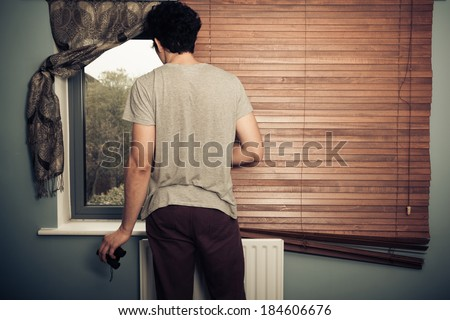 Nosy neighbor with binoculars standing by his window - stock photo