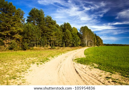 not asphalted rural road along the wood and a field. summer - stock photo