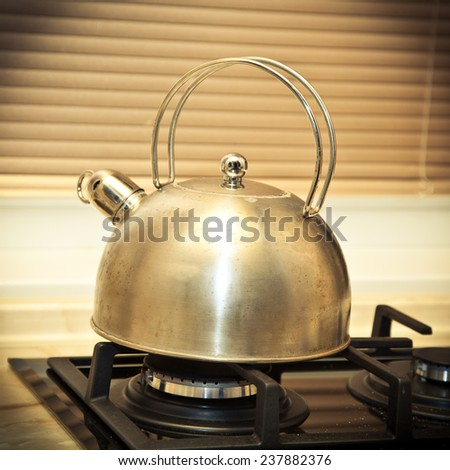 Not very clean whistling kettle on the stove. kitchenware - stock photo