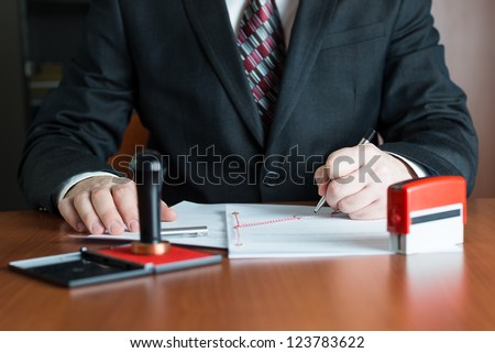 Notary Public in his office signing a contract - stock photo