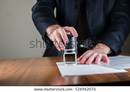 Notary public in office stamping document,vertical photo