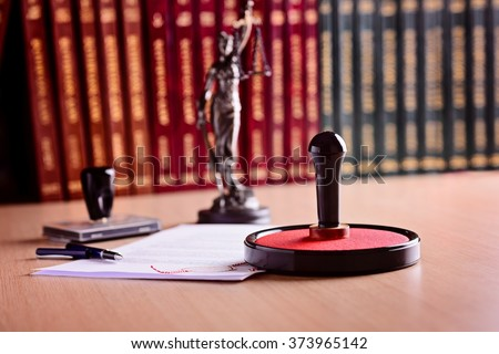 Notary's public working accesories. Metal stamper, rubber stamp, pen and statue of Themis - stock photo
