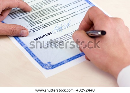 notary signing a power of attorney, focus is on the tip of the pen - stock photo