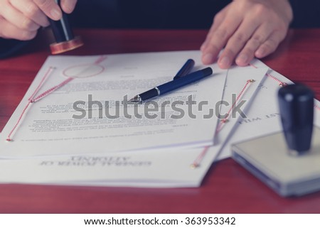 Notary stamps signed power of attorney in his notary's office - stock photo