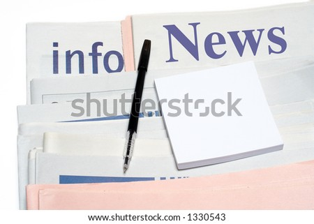 Note and pen, over stacked newspapers on white background