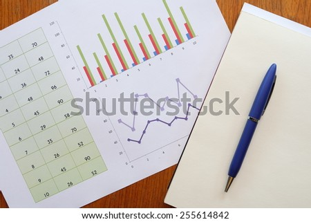 note book and chart on the wooden table