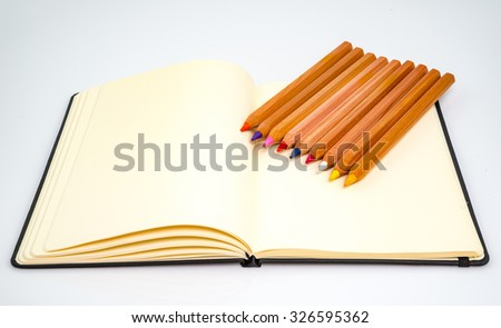 Note book and colored pencils  on white background