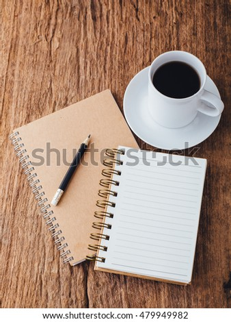 note book and cup coffee on wooden table