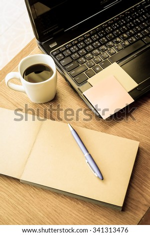 note book and laptop on wooden table with vintage style - stock photo
