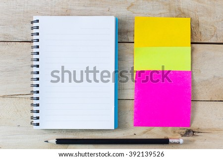 Note book and note paper on a wooden background - stock photo