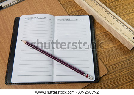 note book and pencil on wooden - stock photo