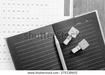 note book and planner on the wooden table with black and white color concept - stock photo