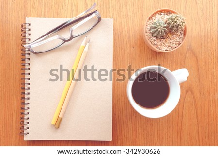 note book and tool  on the wooden table with vintage color style  - stock photo