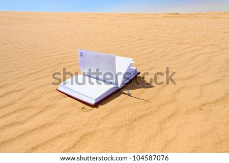 note book in sand dune of Wadi Rum desert, Jordan - stock photo