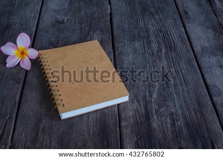 Note book on wooden background with flower - stock photo