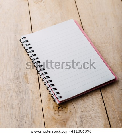note book on wooden table - stock photo