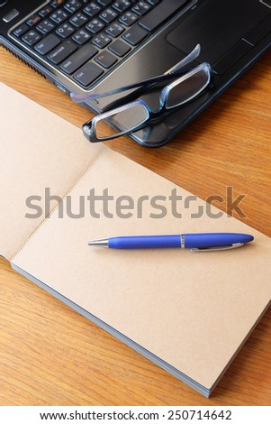 note book on wooden table with glasses   - stock photo