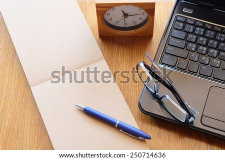 note book on wooden table with glasses and clock  - stock photo