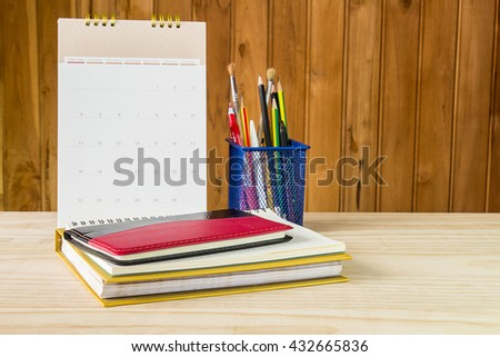 Note book,pen,pencil and stack of book with calendar on wooden table background