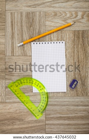 Note book, pencil and plastic protractor ruler on a wooden texture - stock photo