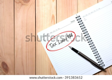 Note Book with Black Pen. Writing TAX LAW and money symbol in Red Circle with wooden pallet background.