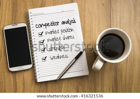 Note book with four check marks, smartphone, a pen and a cup of coffee on wooden background. - stock photo