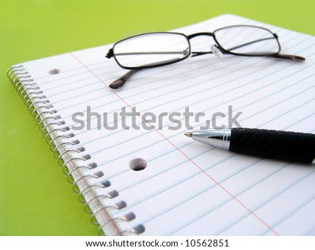 note book with pen and glasses